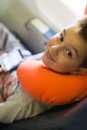 Kid travelingwith his neck pillow travelling with player and orange on the airplane Royalty Free Stock Images