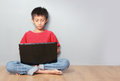 Kid using laptop portrait of asian on grey background Royalty Free Stock Images