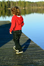 Kid walking on the bridge playing in autumn sun by lake Royalty Free Stock Photography