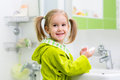 Kid washing her face and hands in bathroom Royalty Free Stock Photo