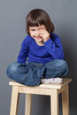 Kid wellbeing concept thrilled preschool child sitting with relaxing crossed legs expressing healthy childhood studio shot Royalty Free Stock Photography