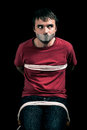 Kidnapped man hostage with tape over mouth and tied up with rope Stock Photos