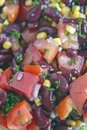Kidney bean and corn salad close up of a dark nutritious rich with beans tomatoes red onion parsley garlic olive oil lemon juice Stock Images