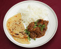 Kidney masala meal from above a bhuna type curry served with rice and paratha bread garnished with coriander leaves Stock Photo