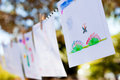 Kids art work hanging on a row on a outdoor location Royalty Free Stock Photo