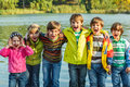 Kids in autumn clothing group of shouting and boots beside river Stock Photo