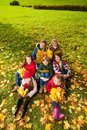 Kids on autumn lawn group of boys and girls sitting in the park with maple yellow leaves bouquet in casual clothes Stock Image