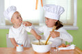 Kids are baking at chef uniform muffins Royalty Free Stock Photos
