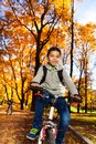Kids on a bike in autumn park portrait of years old black boy riding bicycle the with maple and oak orange trees Royalty Free Stock Image