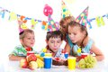 Kids with birthday cake group of adorable having fun at party Royalty Free Stock Photography