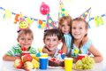 Kids with birthday cake group of adorable having fun at party Stock Photo