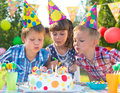 Kids at birthday party blowing candles on cake celebrating and Stock Images