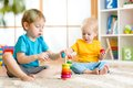 Image : Kids boys with toys in playroom loving  time