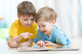 Kids brothers practice read together looking at book laying on the floor reading Royalty Free Stock Photo