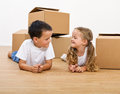 Kids with cardboard boxes on the floor smiling laying Royalty Free Stock Photos
