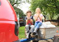 Kids on carriage little boy and girl sitting behind red car and clapping their hands Stock Photography