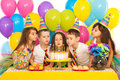 Kids celebrating birthday party and blowing Royalty Free Stock Photo