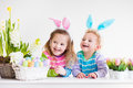 Kids celebrating easter at home happy children celebrate boy and girl wearing bunny ears enjoying egg hunt playing with color eggs Royalty Free Stock Photos