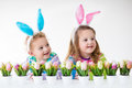 Kids celebrating easter at home happy children celebrate boy and girl wearing bunny ears enjoying egg hunt playing with color eggs Royalty Free Stock Image