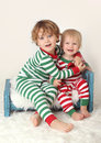 Kids children in christmas outfits winter themed striped pjs on a bed Royalty Free Stock Photography
