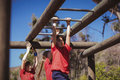 Kids climbing monkey bars during obstacle course training Royalty Free Stock Photo
