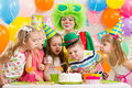 Kids with clown celebrating birthday party and blowing candle on cake Stock Image