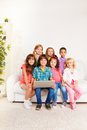 Kids with computer group of happy smiling beautiful sitting on the couch laptop Royalty Free Stock Image