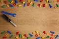 Kids construction toys tools: colorful screwdrivers, screws and nuts on wooden background. Top view. Flat lay. Copy