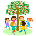 Kids dance around a tree