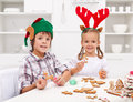 Kids decorating gingerbread christmas cookies wearing funny seasonal hats Stock Photography