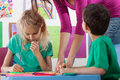 Kids drawing in kindergarden a girl and a boy with colourful pens Royalty Free Stock Photo