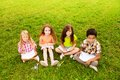 For kids drawing outside four happy three girls and boy sitting together on the lawn and pictures Stock Photo