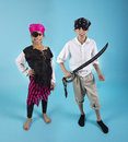 Kids dressed in pirate costumes a boy and girl ready for halloween isolated on a blue background Royalty Free Stock Photography