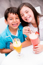 Kids drinking juice and smiling Royalty Free Stock Photos