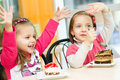 Kids eating cute happy little girls are cake in parlor Stock Images