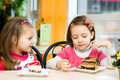 Kids eating cute little girls are cake in parlor Royalty Free Stock Photo