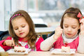 Kids eating cute little girls are cake in parlor Royalty Free Stock Images