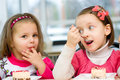 Kids eating cute little girls are cake in parlor Royalty Free Stock Image