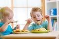 Kids eating healthy food in kindergarten or