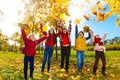 Kids enjoying autumn maple park group of five boys and girls throwing leaves in the Royalty Free Stock Photography