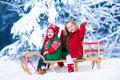 Kids enjoying sleigh ride on christmas day little girl and baby boy a child sledding toddler kid riding a sledge children play Royalty Free Stock Photo