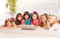 Kids on the floor with laptop group of happy little boys and girls laying in living room Royalty Free Stock Photos