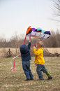 Kids flying kite two boys working to get a in the air Royalty Free Stock Photo