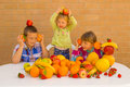 Kids and fruits playing eating various lovely bananas oranges apples grapefruit strawberries pomelo Stock Photos