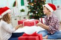 Kids with giftbox portrait of happy siblings holding and looking at one another on christmas evening Stock Photography