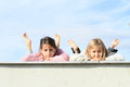 Kids girls lying on roof smiling barefoot grey under the blue sky Royalty Free Stock Photos
