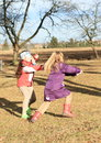 Kids girls playing blind man s buff young in winter clothes a game Stock Image