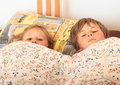 Kids going to sleep two boy and girl lying in a bed on pillow under blanket with flowers and Stock Photo