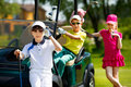 Kids golf competition children playing and taking part on in course at summer day Stock Image