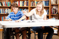 Kids goof around at school teen boy and girl goofing in the library the boy is disabled in a wheelchair Royalty Free Stock Images